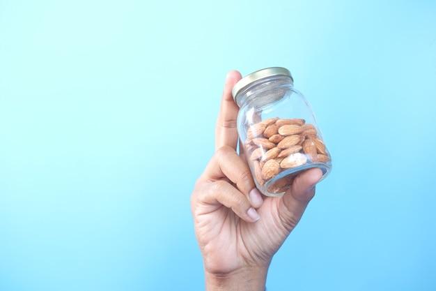 Hand hält ein glas mandelnüsse vor blauem hintergrund