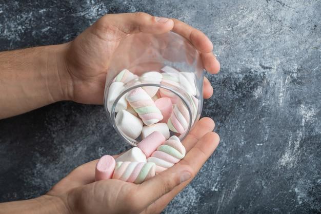 Hand hält ein glas mit leckeren marshmallows auf grauem hintergrund.