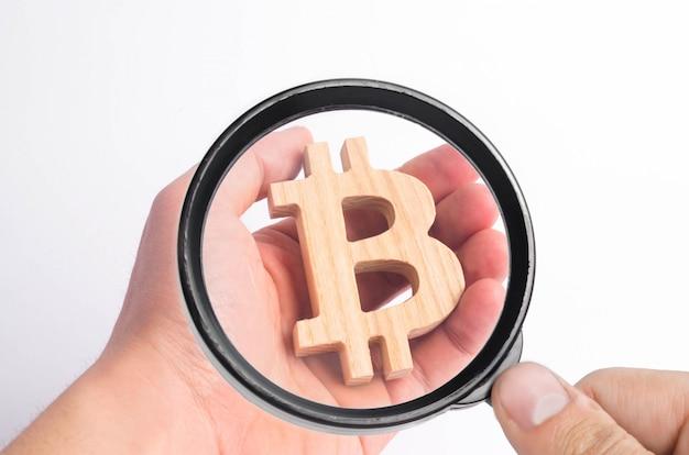 Hand hält ein hölzernes bitcoin auf einem weiß. krypto-währung, sperrtechnologie.