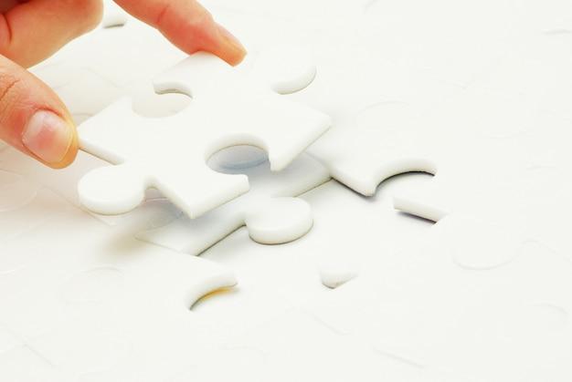 Hand hält ein leeres puzzleteil