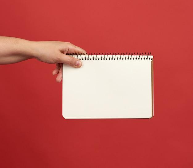 Hand hält ein offenes spiralblock mit leeren weißen blättern