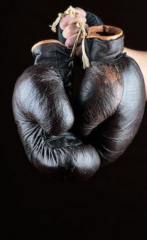 Hand hält ein paar alte lederne braune boxhandschuhe