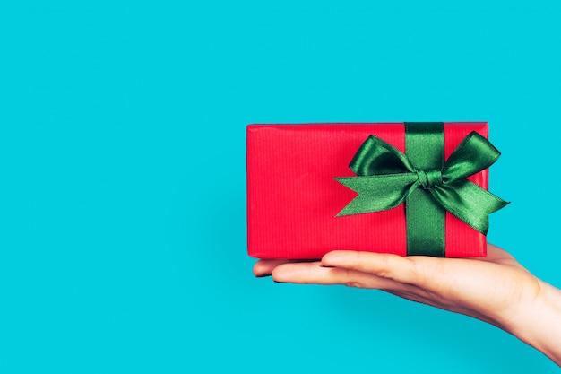 Hand hält ein rotes geschenk mit grüner schleife