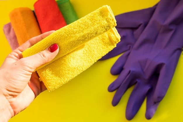 Hand hält ein sauberes trockenes mikrofasertuch. reinigungs- oder reinigungskonzepthintergrund. lila gummihandschuh und satz reinigungswerkzeuge und -ausrüstung. kopierfläche für text oder werbung.