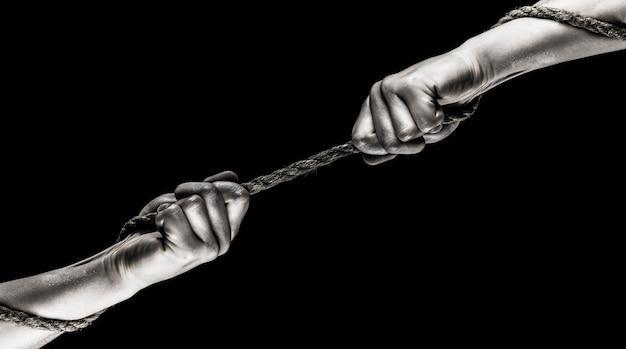 Hand hält ein seil, kletterseil, stärke und entschlossenheit. zwei hände, helfende hand, arm, freundschaft. rettung, hilfe, helfende geste oder hände. konflikt, tauziehen. seil, schnur. schwarz und weiß.