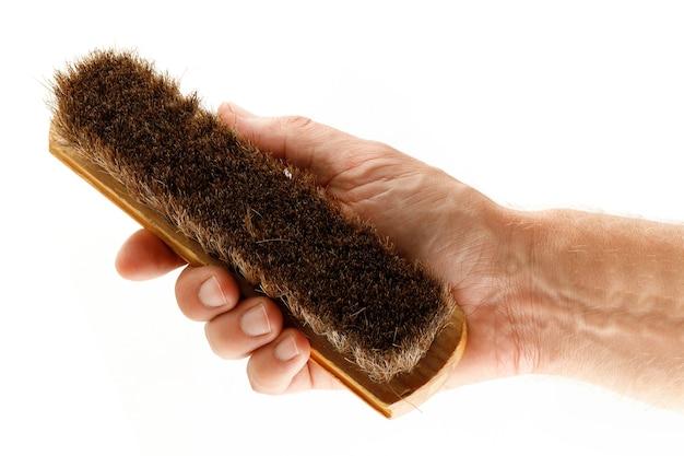 Hand hält eine bürste, um kleidung zu isolieren