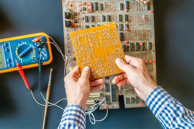 Hand hält eine elektrische leiterplatte reparieren ix und montieren elektronikkonzept lebensmittel