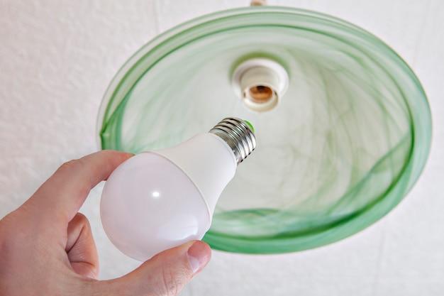 Hand hält eine energieeffiziente led-lampe, ersatz der glühbirne in der deckenleuchte durch schatten von grünem milchglas, nahaufnahme.