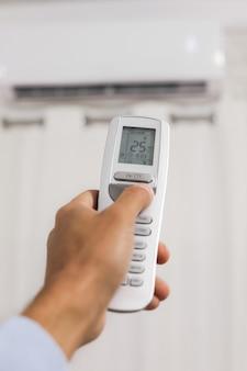 Hand hält eine fernbedienung der klimaanlage
