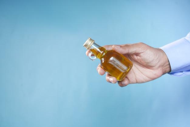 Hand hält eine flasche olivenöl vor blauem hintergrund