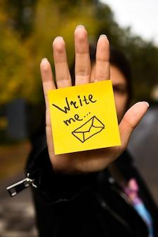 Hand hält eine gelbe notiz mit einer nachricht
