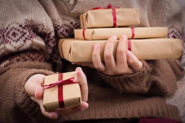 Hand hält eine geschenkbox aus. mädchen in einer gestrickten strickjacke hält einen stapel geschenkboxen im braunen kraftpapier.