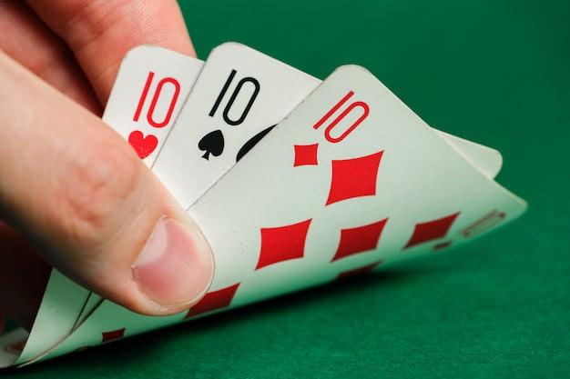Hand hält eine kombination im schürhaken - drei einer art auf grün.