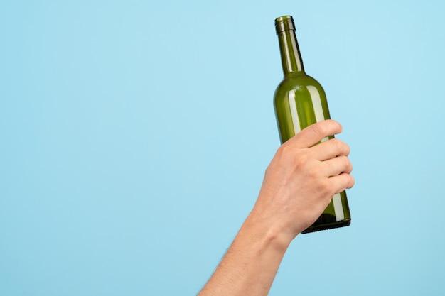Hand hält eine leere glasweinflasche auf einem blauen hintergrund. konzept von recycling und ökologie.