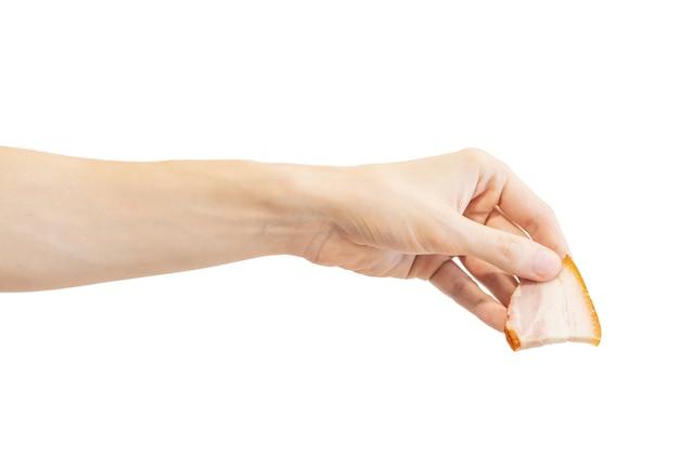 Hand hält eine scheibe des geräucherten speckes lokalisiert auf weiß