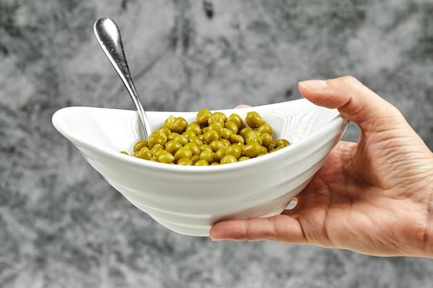Hand hält eine schüssel mit gekochten grünen erbsen.