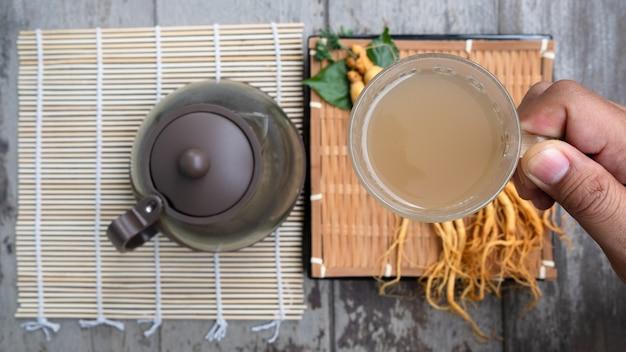 Hand hält eine tasse ginseng-tee