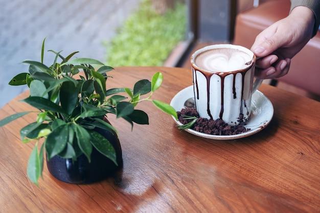 Hand hält eine tasse heiße schokolade auf holztisch im café