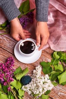 Hand hält eine tasse morgenkaffee mit frühlingsfliederblumenzweigen, die auf holztisch blühen
