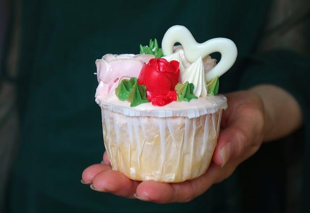 Hand hält einen cupcake mit schönen rosen verziert