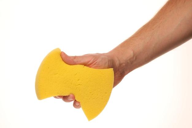 Hand hält einen gelben schwamm isoliert