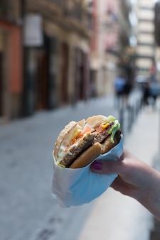 Hand hält einen hamburger