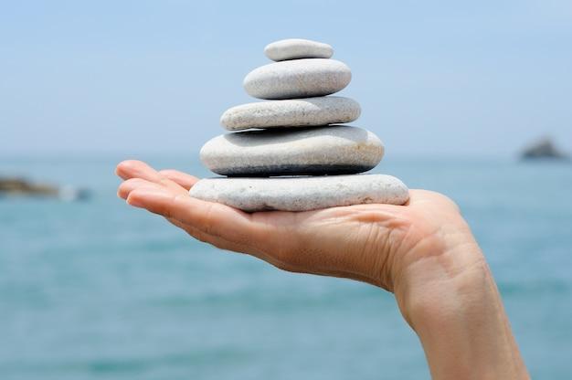 Hand hält einen haufen von kieselsteinen