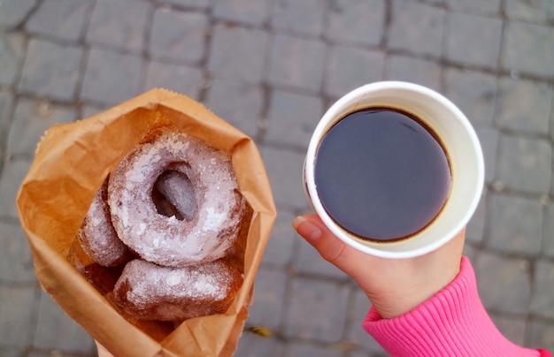 Hand hält einen heißen kaffee für unterwegs und eine tüte zuckerglasierte donuts