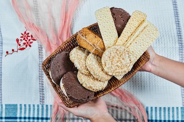 Hand hält einen korb mit gemischten keksen auf einer tischdecke.