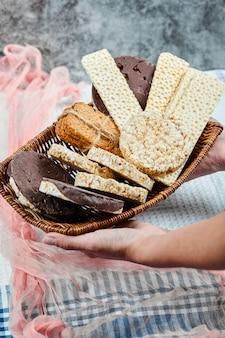 Hand hält einen korb mit gemischten keksen.