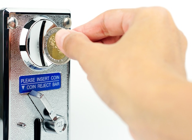 Hand hält einen münzautomaten auf weißem hintergrund