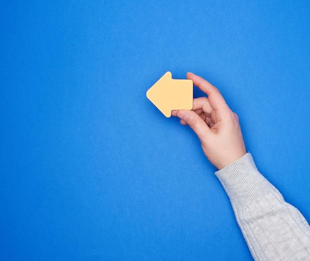 Hand hält einen orange papieraufkleber in form eines pfeilzeigers