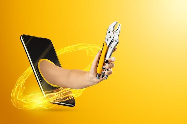 Hand hält einen schraubenschlüssel durch ein smartphone
