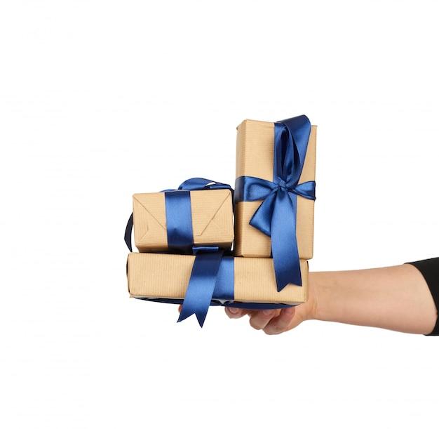 Hand hält einen stapel eingewickelter geschenke in braunem bastelpapier mit gebundenen seidenschleifen