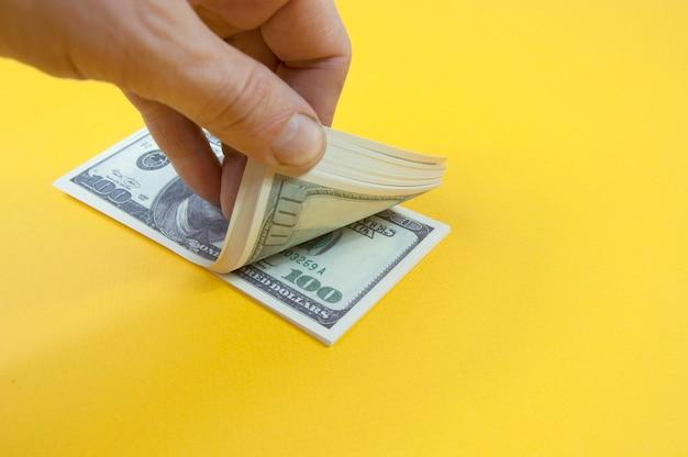 Hand hält einen stapel von hundert dollarnoten