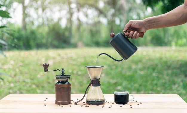 Hand hält einen wasserkocher und gießt heißes wasser für kaffee machen