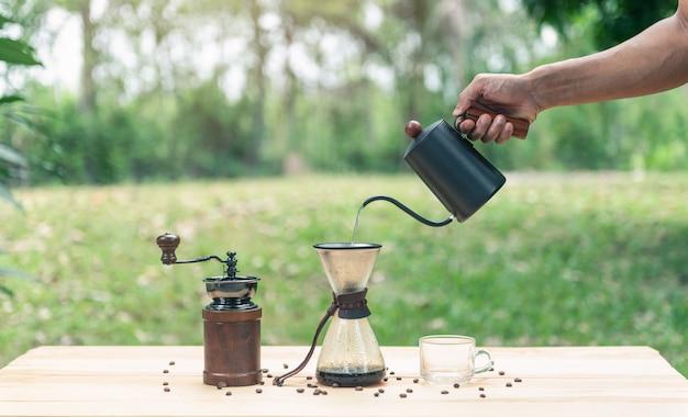 Hand hält einen wasserkocher und gießt heißes wasser für kaffee mit leerem glas kaffee
