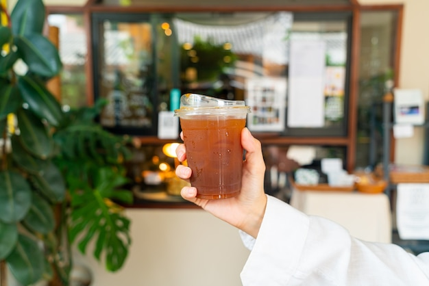 Hand hält eisgekühlten americano-kaffee im glas zum mitnehmen
