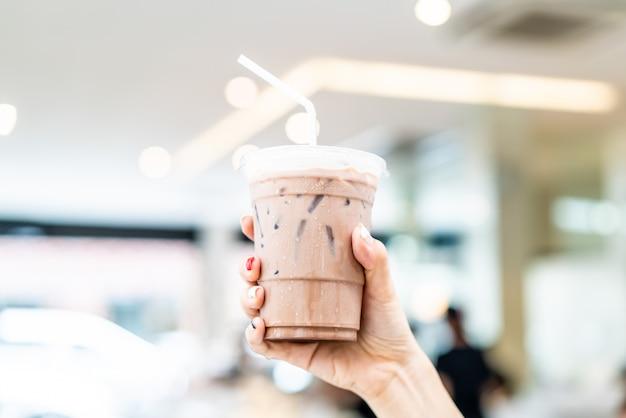 Hand hält eisige belgische schokoladenmilchshake-tasse