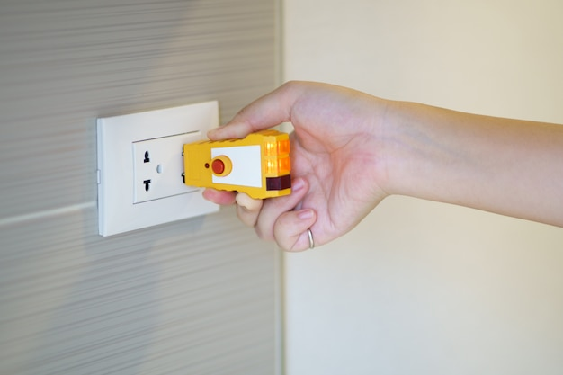 Hand hält elektrischen tester zur überprüfung des steckers an der steckdose an der wand. überprüfen sie die qualität