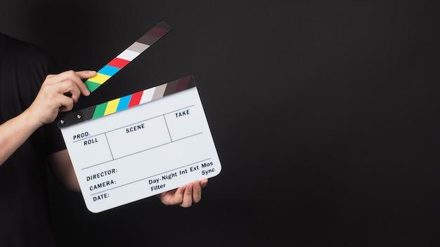 Hand hält filmschiefer. es wird in der videoproduktion und in der filmindustrie auf schwarzem hintergrund verwendet.