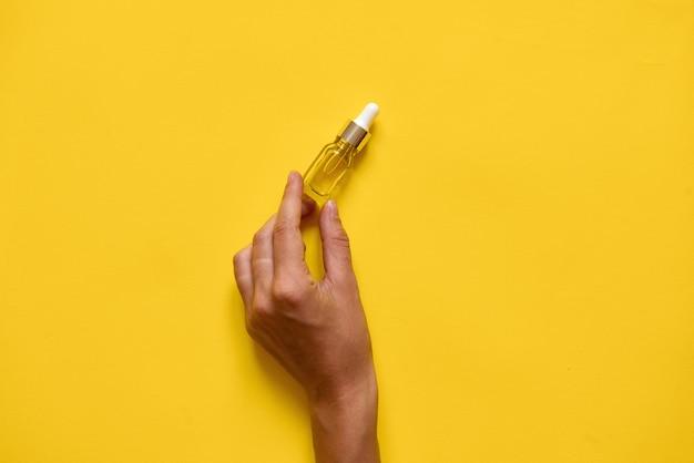 Hand hält flasche mit serum oder öl natürlicher essenz.