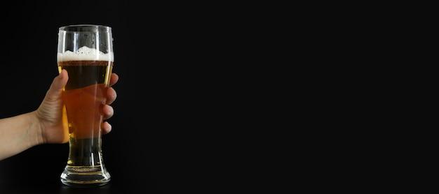 Hand hält frostiges glas kaltes goldenes bier mit blasen auf schwarzem hintergrund. freier speicherplatz für text, kopienraum, banner. alkohol trinken auf party, feiertagen, oktoberfest oder st. patrick's day.