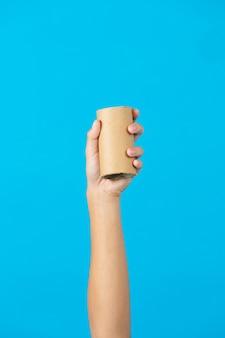 Hand hält gebrauchten seidenpapierkern auf blauem hintergrund