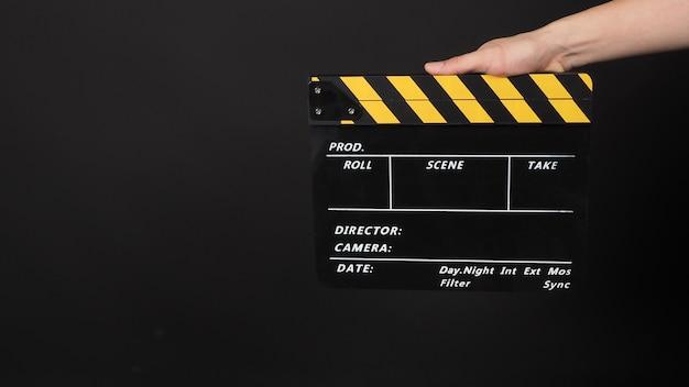 Hand hält gelbe und schwarze farbfilmschiefer. sie wird in der videoproduktion und in der filmindustrie auf schwarzem hintergrund verwendet.