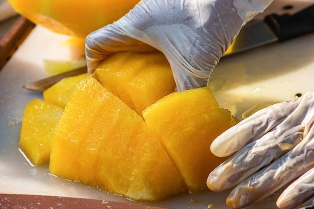 Hand hält gelbe wassermelone und schneidet mit einem messer ein stück.