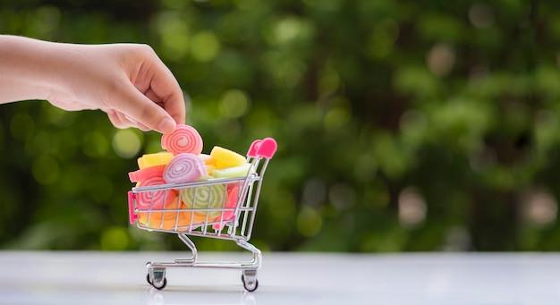Hand hält gelee beschichtete süßigkeiten aus spielzeug einkaufswagen