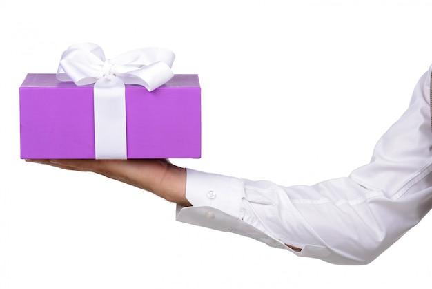 Hand hält geschenk auf gewicht auf weiß.