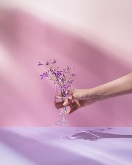 Hand hält glas mit transparenter flüssigkeit und lila blüten pastellrosa hintergrund.