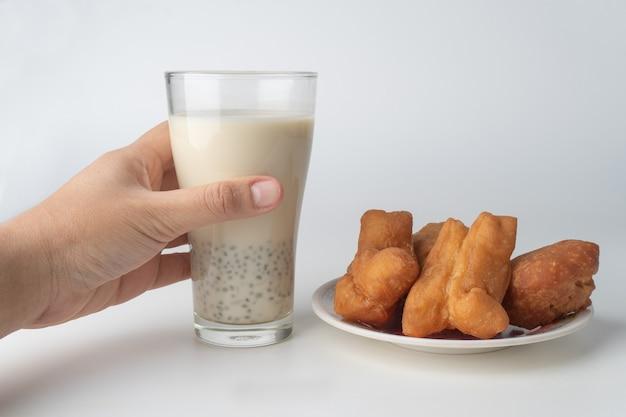 Hand hält glas sojamilch und donuts